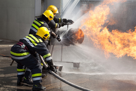 Firefighters attack a propane fire during a training exercise Archivio Fotografico