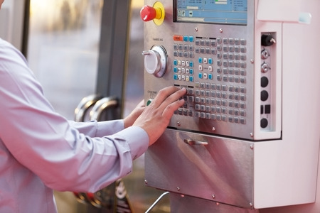 industrial machinery: Hand on the control panel of a programmable machine