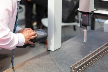 quality check: Inspecting metal part with CMM. Quality control. Stock Photo