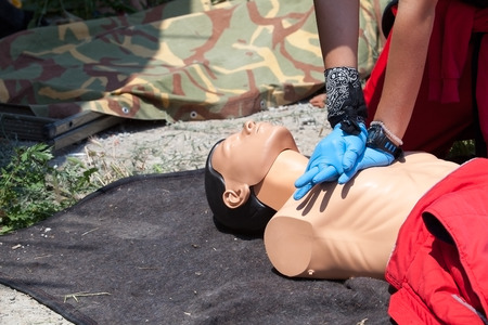 chest compression: Cardiopulmonary resuscitation (CPR) being performed on a medical-training manikin