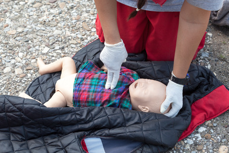 Child dummy cardiac massage. Cardiopulmonary resuscitation CPR. 版權商用圖片