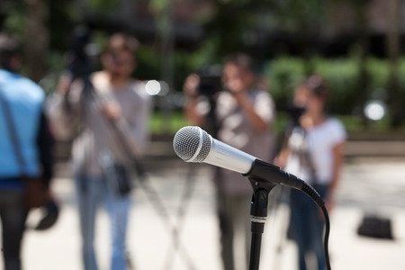 medium group of objects: Microphone in focus against blurred cameraman Stock Photo