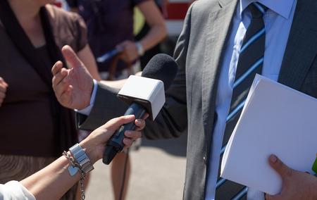 entrevista: Reportero haciendo entrevista con empresario Foto de archivo
