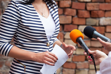 public: Journalists making media interview with woman