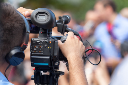 communication occupation: Filming an event with a video camera.  Stock Photo