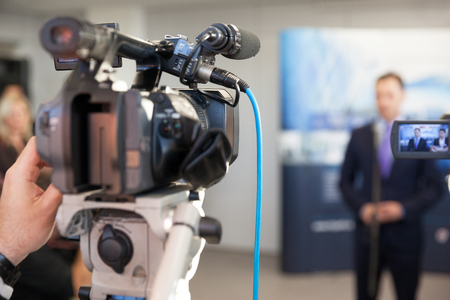 tv camera: Filming an event with a video camera. Spokesperson.
