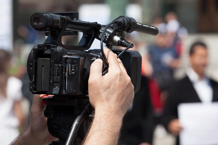 live action: Filming street protest using video camera