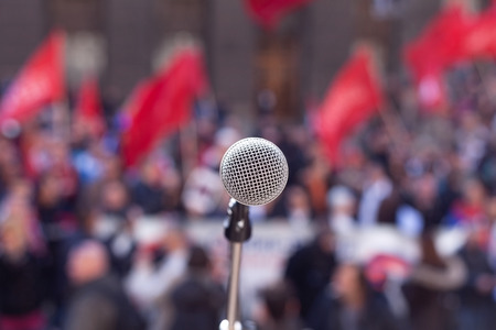 nonviolent: Microphone in focus against unrecognizable crowd