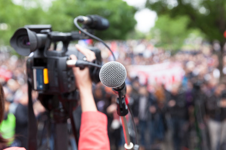 nonviolent: Microphone in focus against blurred crowd. Filming protest.