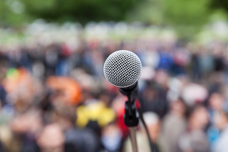 Microphone in focus against blurred audience. Protest.
