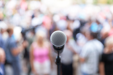 Microfoon in focus tegen wazig publiek Stockfoto