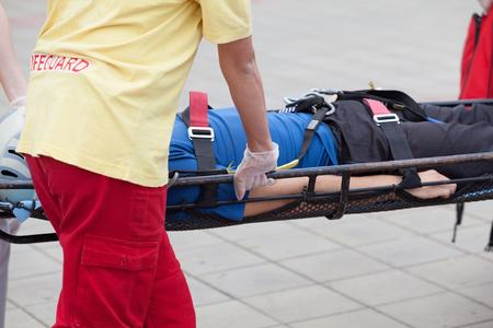 evacuate: Paramedics evacuate an injured person