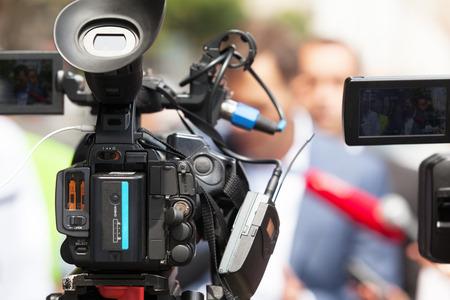 relaciones publicas: Video camera in focus, blurred spokesperson in background. Press conference.