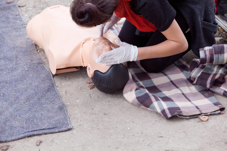 accident rate: Taking a pulse. Female paramedic showing cardiopulmonary resuscitation - CPR on training dummy.