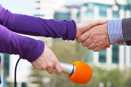 Businessman and a female reporter shaking hands before media interview