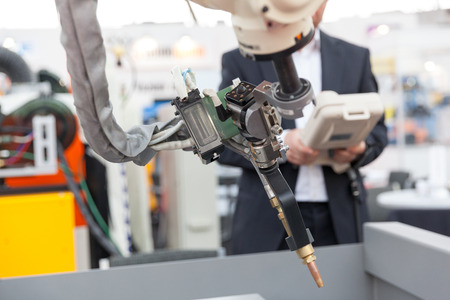 programing: Industrial welding robotic arm, blurred operator in the background