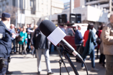 demonstration: Protest. Demonstration. Microphone in focus, blurred protesters in background. Stock Photo