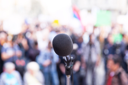 Microphone in focus, against blurred crowd. Protest. Public demonstration. Stock Photo