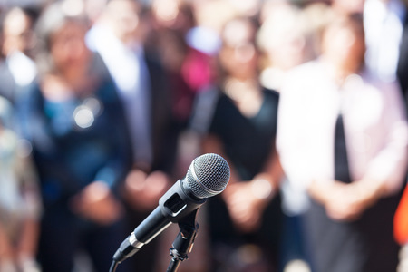 Microphone in focus against blurred group of people