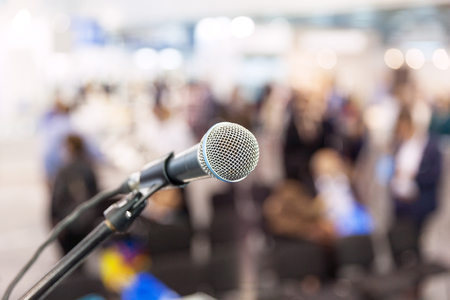 Microphone in focus against blurred audience. News conference.
