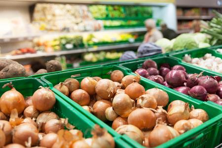 Onions on vegetable supermarket shelfs