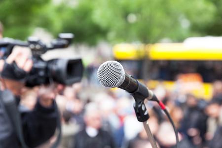 Micrófono en foco contra la multitud borrosa. Filmando la protesta callejera