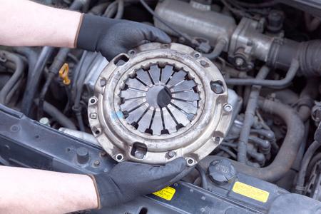 보호 작업 장갑을 끼고 자동차 정비사는 자동차 엔진을 통해 오래 된 클러치 바구니를 보유하고있다. 스톡 콘텐츠