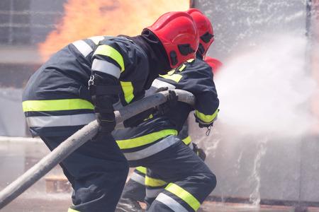 Feuerwehrleute in Aktion. Feuer bekämpfen. Standard-Bild - 97532361