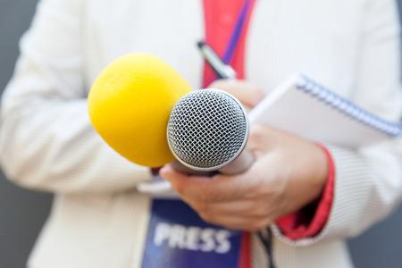 Journalistin bei Pressekonferenz, Notizen schreiben, Mikrofon halten