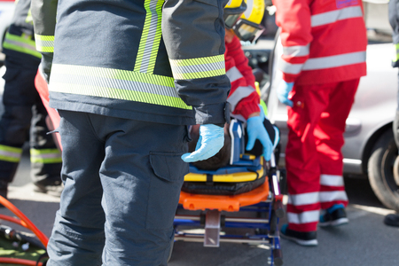 Paramedics and firefighters in a rescue operation after road traffic accident Stock Photo