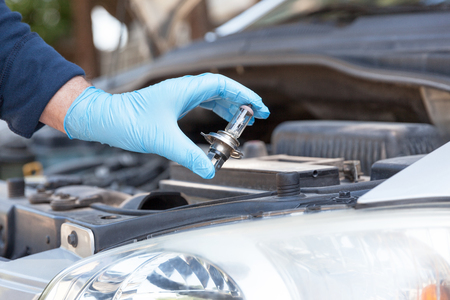 Installing new car headlight bulb 写真素材