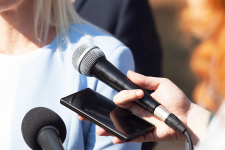 Journalists making press interview with businesswoman or female politician