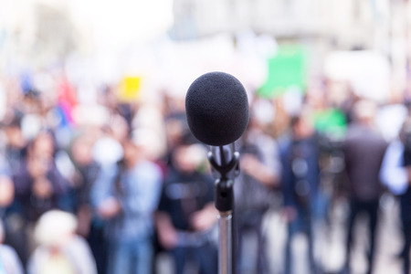 Microphone in focus, blurred people in background