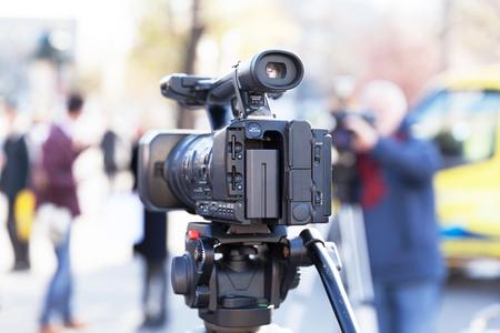 Video camera in the focus, blurred camera operator in the background