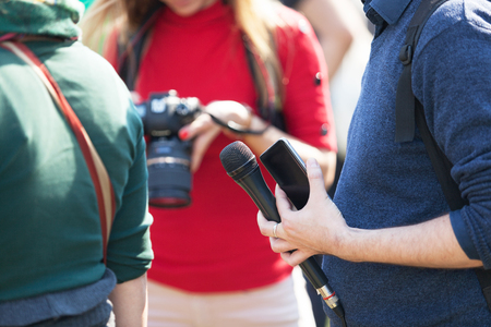 Reporter at media event holding microphone, blurred female photographer in the background