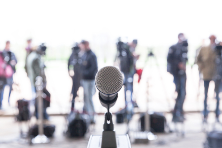 Microphone in focus against blurred camera operators and reporters at press conference