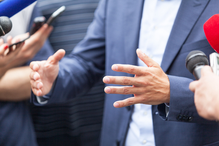 Politician or businessman gesturing during press conference