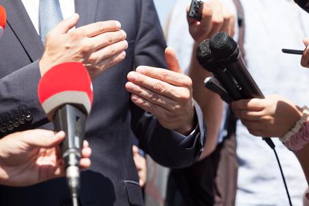 Uomo d'affari o politico che fa gesti durante la conferenza stampa