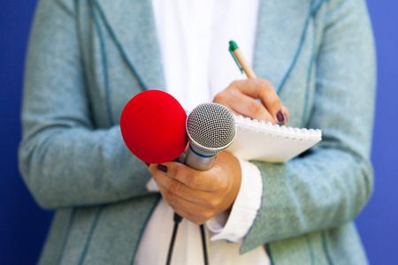 Reportero en conferencia de prensa, tomando notas, sosteniendo el micrófono