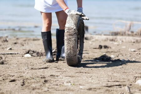 Environmental activist is collecting old tire at river or lake coast