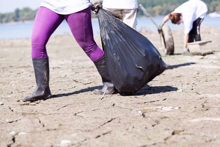 Environmental activist is collecting plastic waste at river or lake coast Banco de Imagens