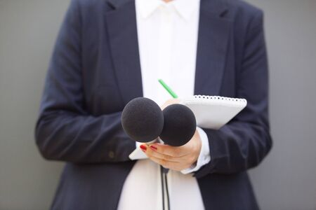Reporter at press conference or news event, holding microphone and writing notes Banque d'images - 138429890