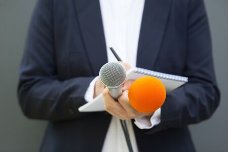 Journalist at news conference or media event, holding microphone and writing notes Banque d'images - 138429886
