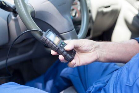 Auto mechanic using car diagnostic scanner tool