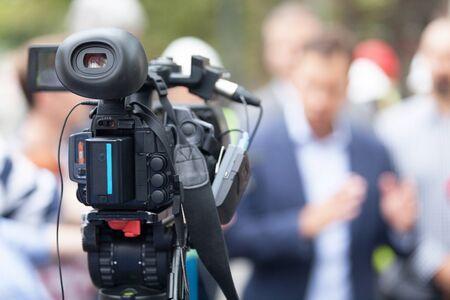 Cámara de video en el foco filmando persona irreconocible borrosa en el fondo Foto de archivo