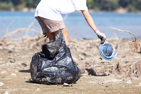 Volunteer is cleaning plastic waste at river or lake bank Banco de Imagens - 139720940