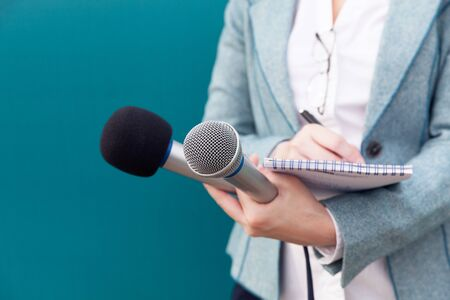 Reporter or TV journalist at news conference, holding microphone and writing notes