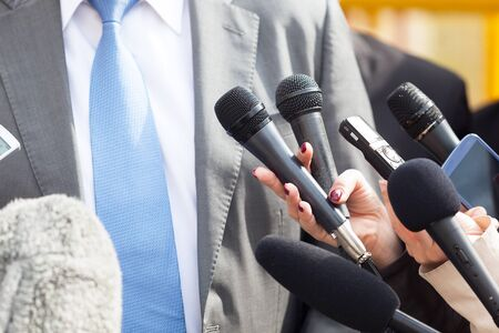 Politician or business person talking with media at press conference