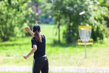 Young woman playing flying disc golf sport game in the park 版權商用圖片
