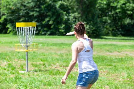 Young woman playing flying disc golf sport game in the park